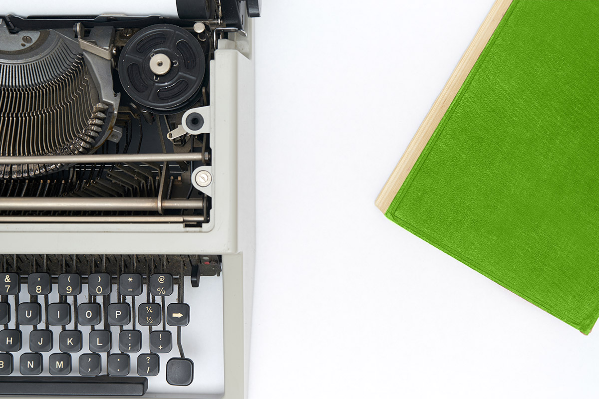 typewriter on white background with green book